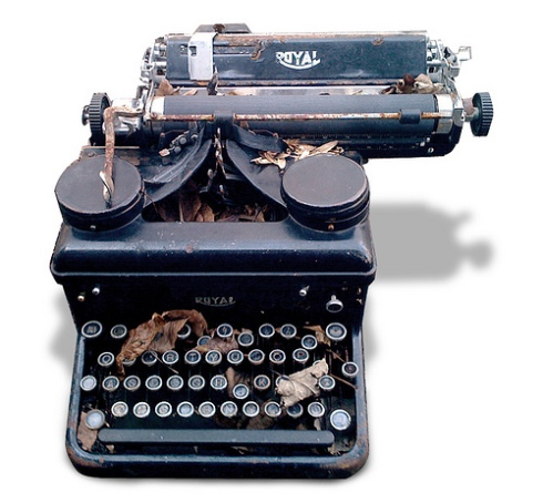 Image of a rusty, black, antique typewriter with round keys
